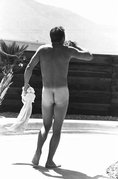 Actor Steve McQueen walking naked outdoors in his backyard