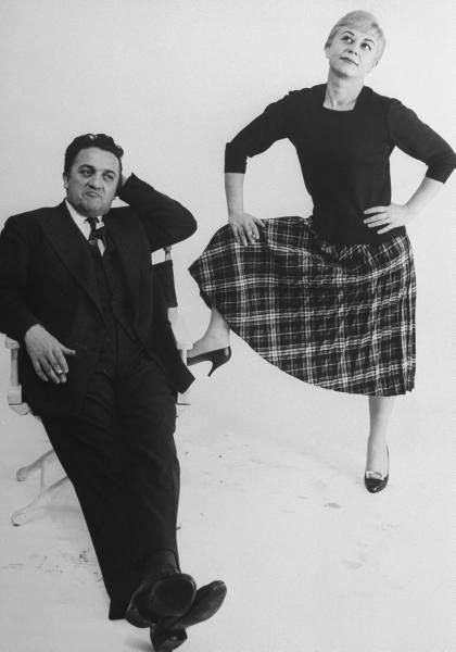 Italian dir. Federico Fellini (sitting in director's chair) and actress wife Giulietta Masina (w. leg propped on chair) posing in studio