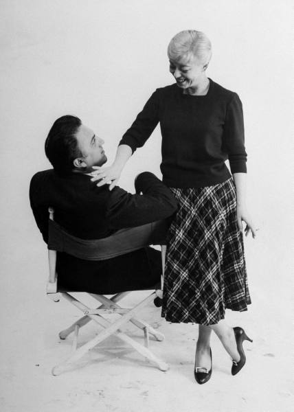 Italian dir. Federico Fellini sitting in director's chair as actress wife Giulietta Masina stands next to him, touching him on the shoulder