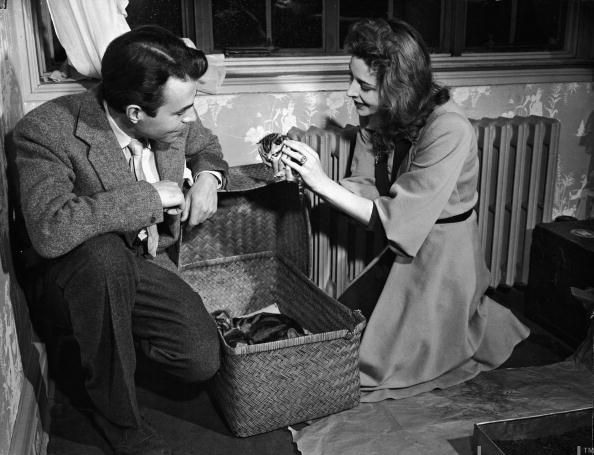 James Mason (1909 - 1984) and his wife take kittens out of a basket containing a mother cat and her litter of kittens, circa 1940